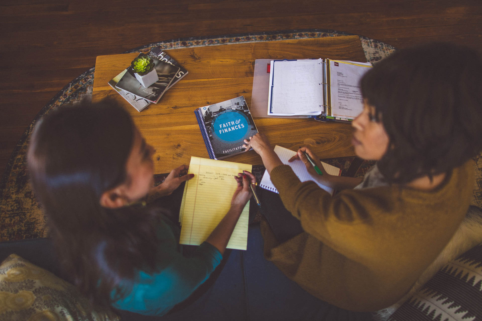 Two women looking at Faith & Finances curriculum