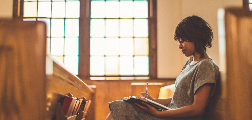 Woman sitting and reading in a church