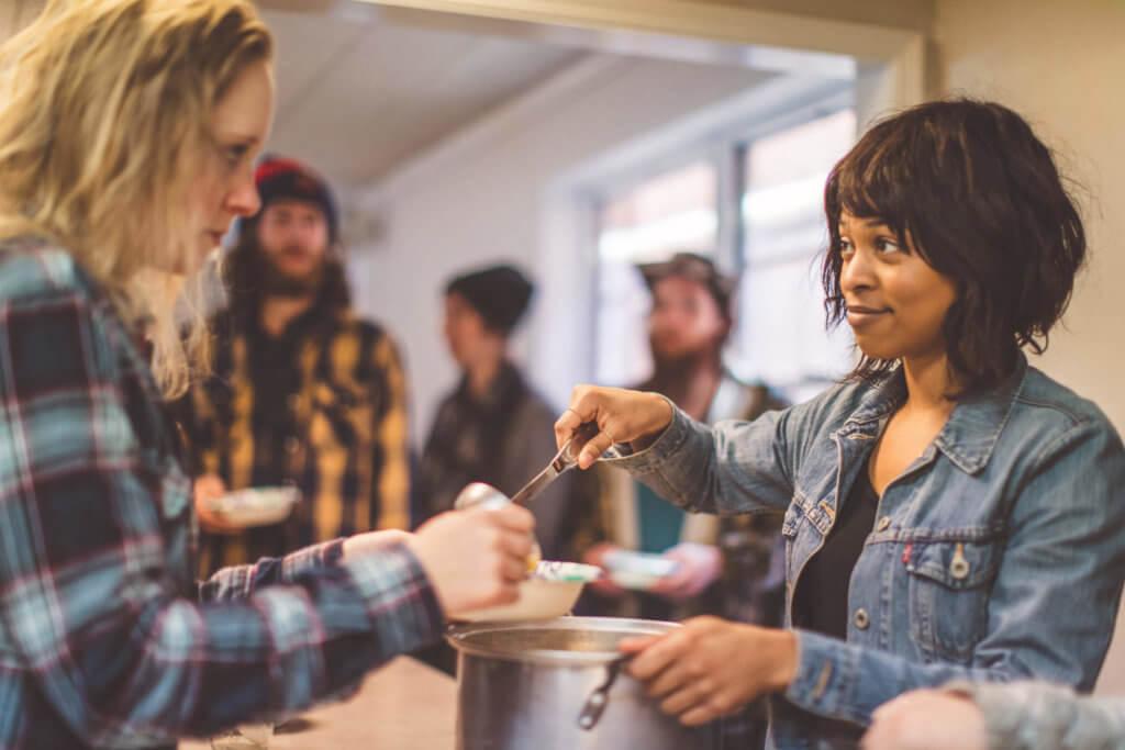 Woman serving soup in a soup kitchen