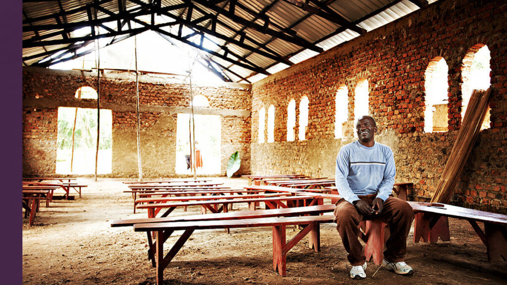 A man sitting on a bench in a church in West Africa